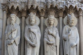 Paris - West facade of Notre Dame Cathedral. Saints statues on The Saint Anne portal and tympanum — Stock Photo