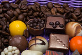 Set of a various chocolate pralines and coffee beans in lavender basket — Stock Photo