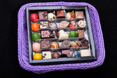 Set of a various chocolate pralines in lavender basket — Stock Photo
