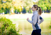 Young Beautiful Woman Running in the Autumn Park — Stockfoto