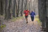 Young Couple Running on the Trail in the Wild Forest — 图库照片