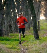 Young Man Running on the Trail in the Wild Forest — Stock Photo
