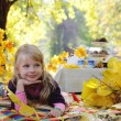 Little girl having picnic under autumn trees — Stock Photo #56702099