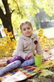 Four year girl sitting under autumn tree — Stock fotografie