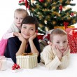 Mother and two children lying under Christmas tree with presents — Stock Photo #59439923