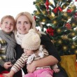Mother with two children lookig up under Christmas tree — Stock Photo #59439963