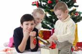 Mother and two children openning presents — Stock Photo
