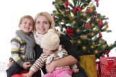 Mother with two children lookig up under Christmas tree — Foto Stock