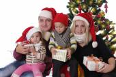 Family with two children in Santa hats — Stock Photo