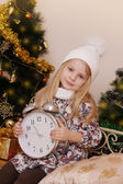 Girl in knitted hat with clock — Stock Photo