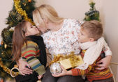 Mother kissing her two children — Stock Photo