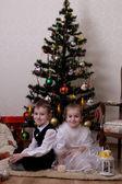Girl and boy under Christmas tree — Stock Photo