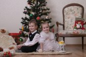 Girl and boy under Christmas tree — Stock Photo