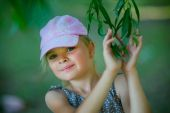 Summer portrait of the girl in a cap on a green background — Stock Photo