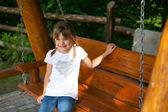 Ragazza allegra in una maglietta bianca e jeans su un altalena in legno — Foto Stock