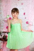 Cute girl in a green dress with a pleated ptichkoyv hands in the — Stock Photo