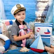 Little boy in a striped t-shirt captain's cap in sea scenery — Stock Photo #78682840