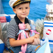 Little boy in a striped t-shirt captain's cap in sea scenery — Stock Photo #78682846