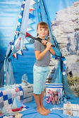 Girl in a striped shirt with a fishing rod on a background seasc — Stock Photo