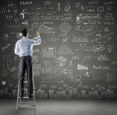 Businessman drawing business plan on wall — Stock Photo