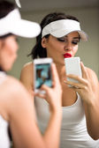 Girl having fun with a phone in front of the mirror — Stock Photo