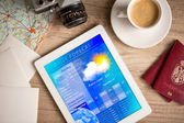 Workplace with tablet pc showing weather forecast — Stock Photo