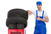 Cheerful mechanic pointing in new tires — Foto de Stock