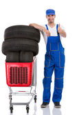 Mechanic with tyre giving a thumbs up — Stock Photo