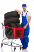 Young mechanic with  tires in shopping cart — Stock Photo
