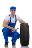 Friendly car mechanic with  tires — Stock Photo