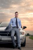 Handsome young man leaning on his car — Stock Photo