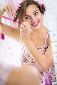 Young woman curling her hair in front  mirror — Stock Photo