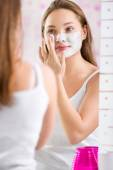 Young cute girl putting facial mask on her face — Stock Photo