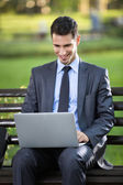 Businessman sitting on bench with laptop — Stockfoto