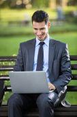 Businessman sitting on bench with laptop — Zdjęcie stockowe
