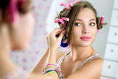 Young  girl front  the mirror puts earring — Stock Photo
