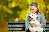 Young woman holding cute maltese dog — Zdjęcie stockowe