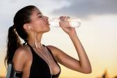 Young sporty woman drinking water — Stock Photo