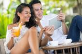 Laughing couple looking at tablet  — Stock Photo