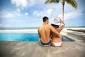 Attractive couple sitting next swimming pool — Stockfoto