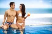 Cheerful couple enjoying next swimming pool  — Stock Photo