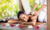 Ung kvinna njuter en hot stone massage — Stockfoto