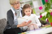 Grandmother and little girl reading book — Stock Photo