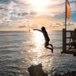 Silhouettes of child jumping in sea — Stock Photo #75912809