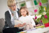Grandmother reading book her little granddaughter — Stock Photo