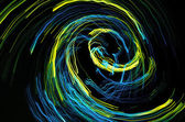 Yellow and blue lines rotating on black background — Stock Photo