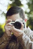 Young male photographer aiming for a shot — Stock Photo