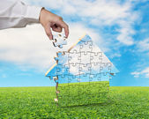 Hand holds the last piece of house puzzle — Stock Photo