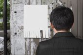 Man look at white paper on noticeboard — Stock Photo