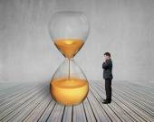 Standing manager looking the hourglass — Stock Photo